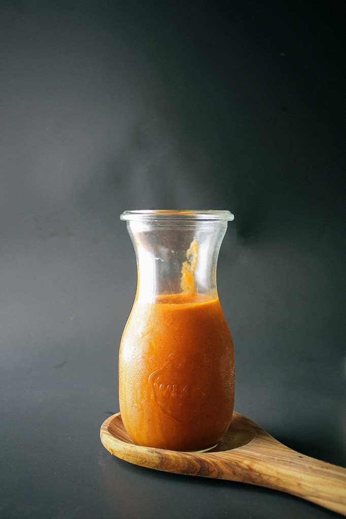homemade red enchilada sauce in glass pitcher resting on wood spoon