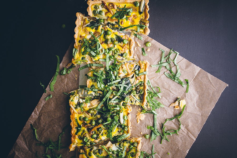 vegetable quiche sliced atop parchment paper