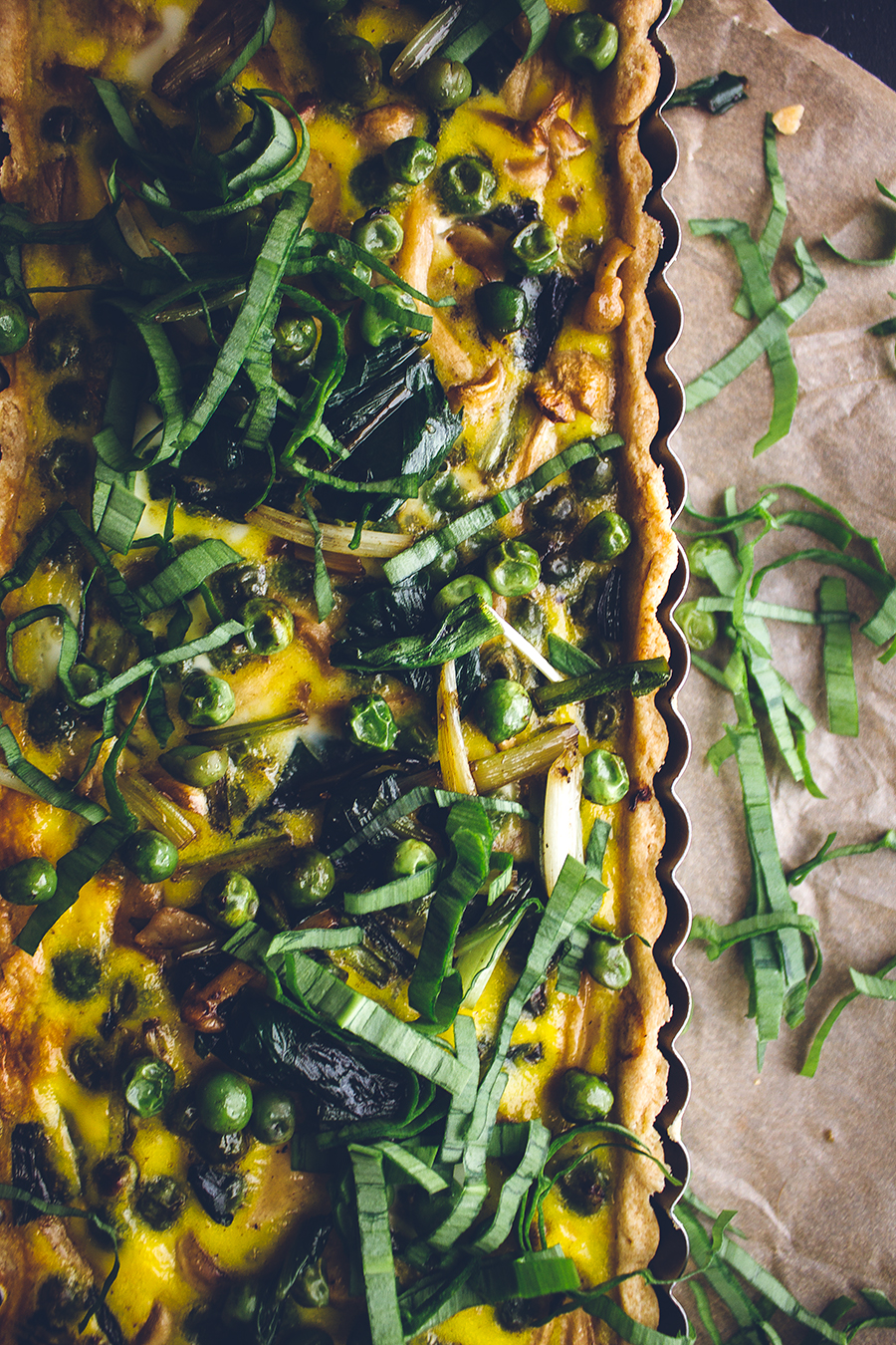 loaded vegetarian quiche on brown towel