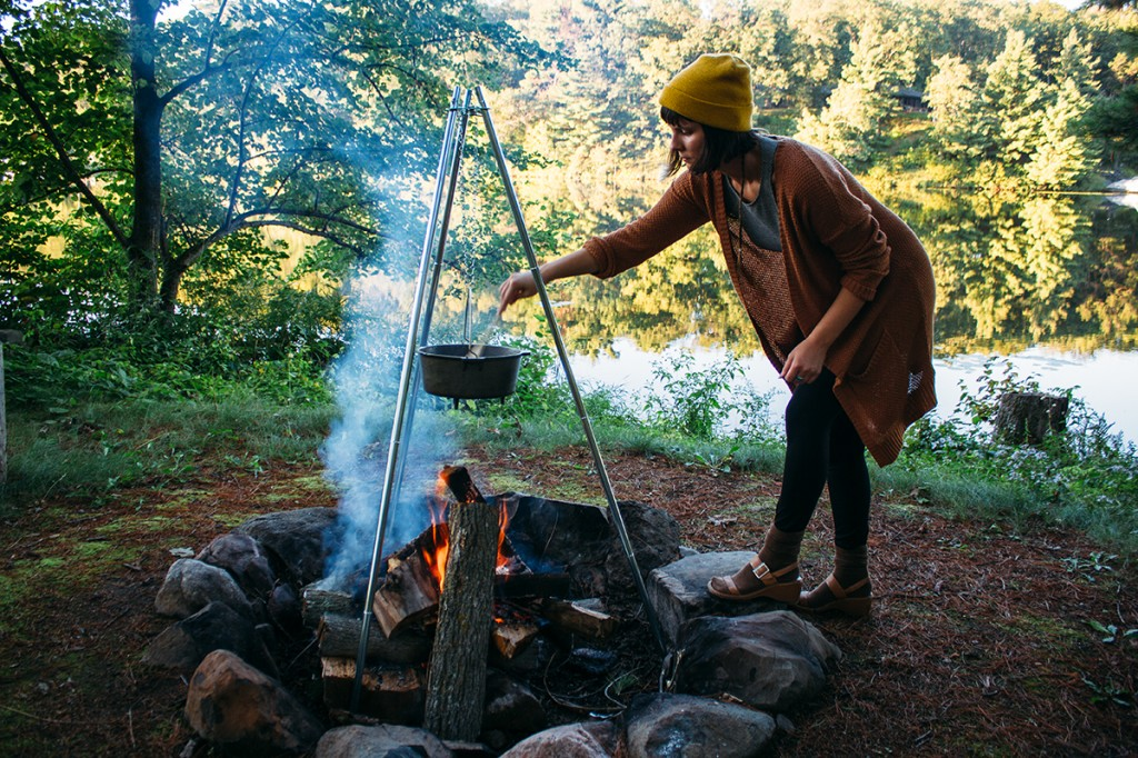 woman stirring pot of three bean chili over campfire
