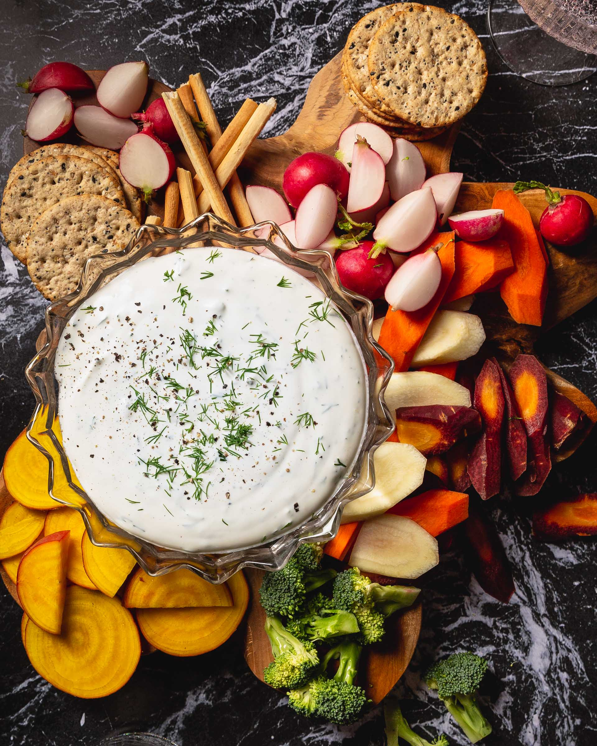 buttermilk dip in bowl with veggies and crackers around it