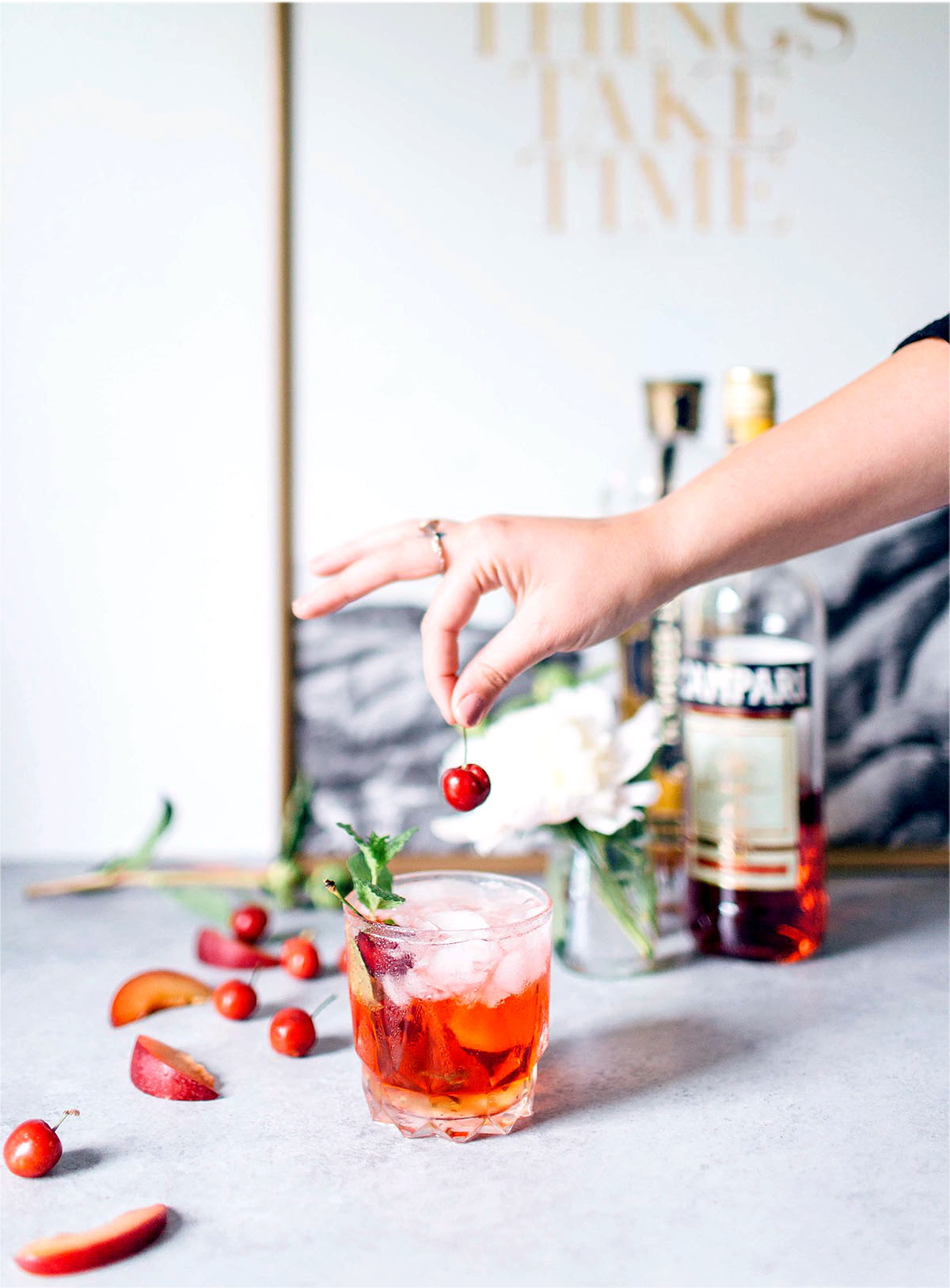 placing a cherry stop a st. germain spritz cocktail