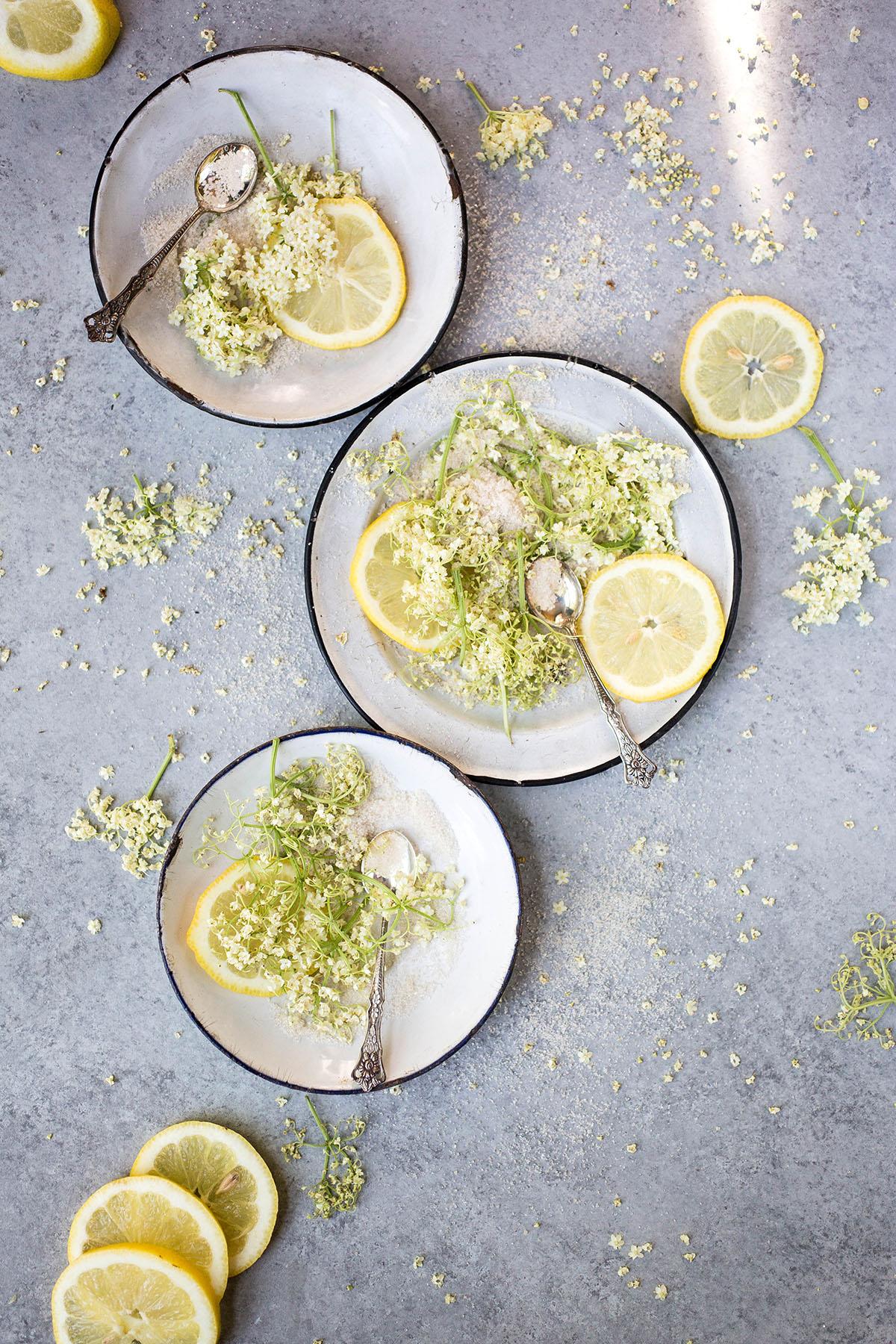 three plates of sugar, elderflower blossoms, and lemon slices