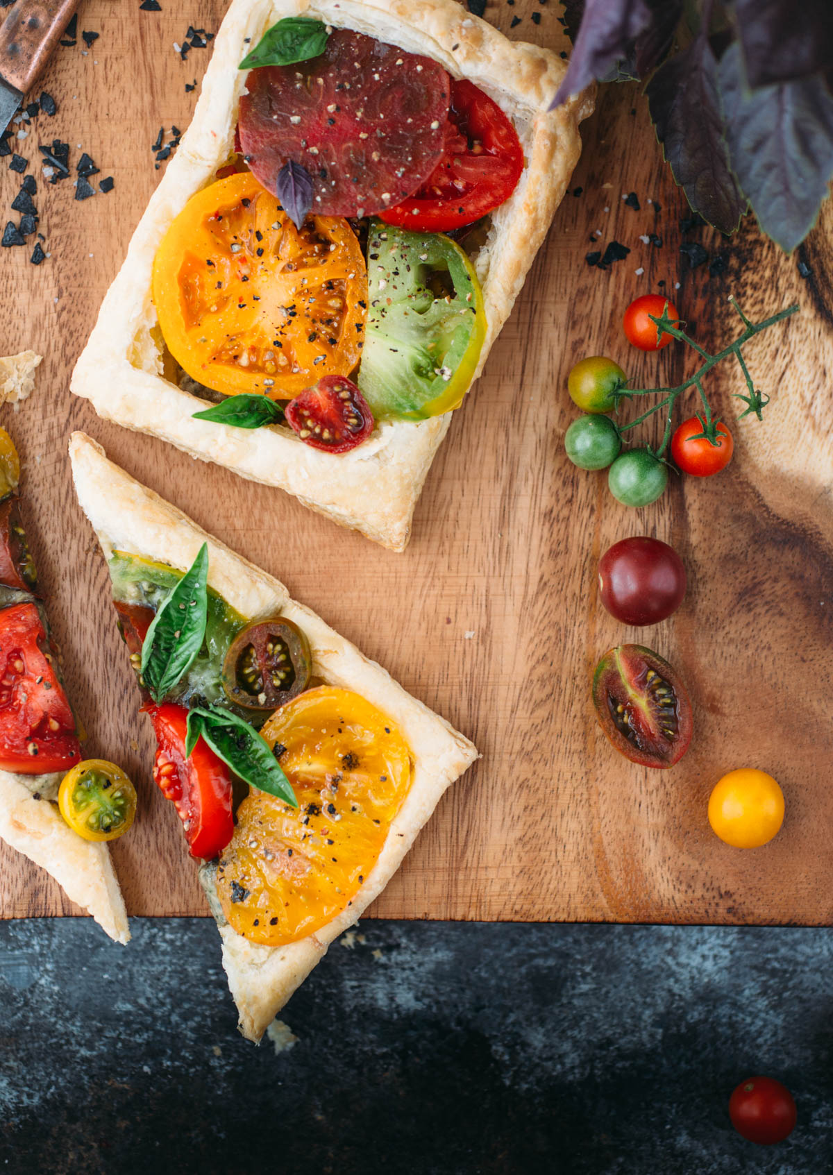 two puff pastry tomato tarts on wood cutting board