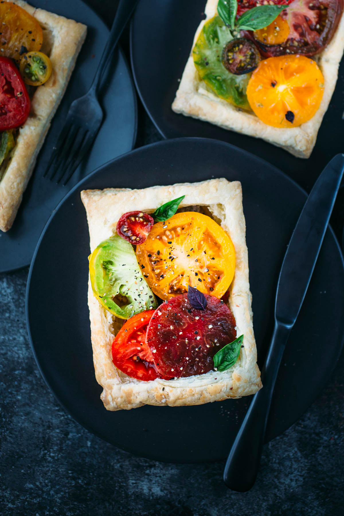puff pastry tomato tart on dark plate with knife