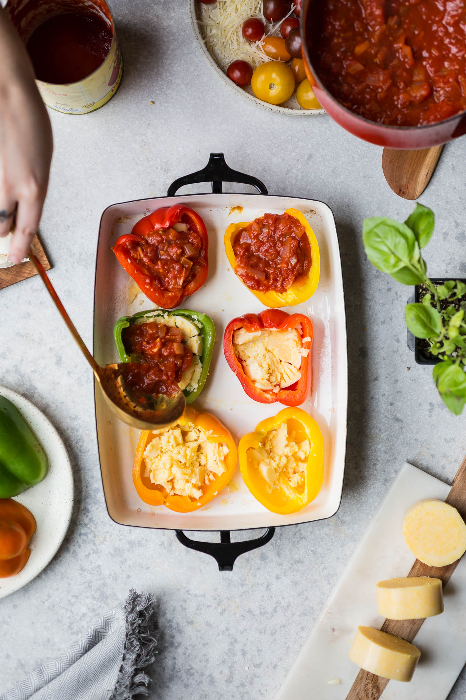 ladling tomato sauce into pizza stuffed bell pepper halves