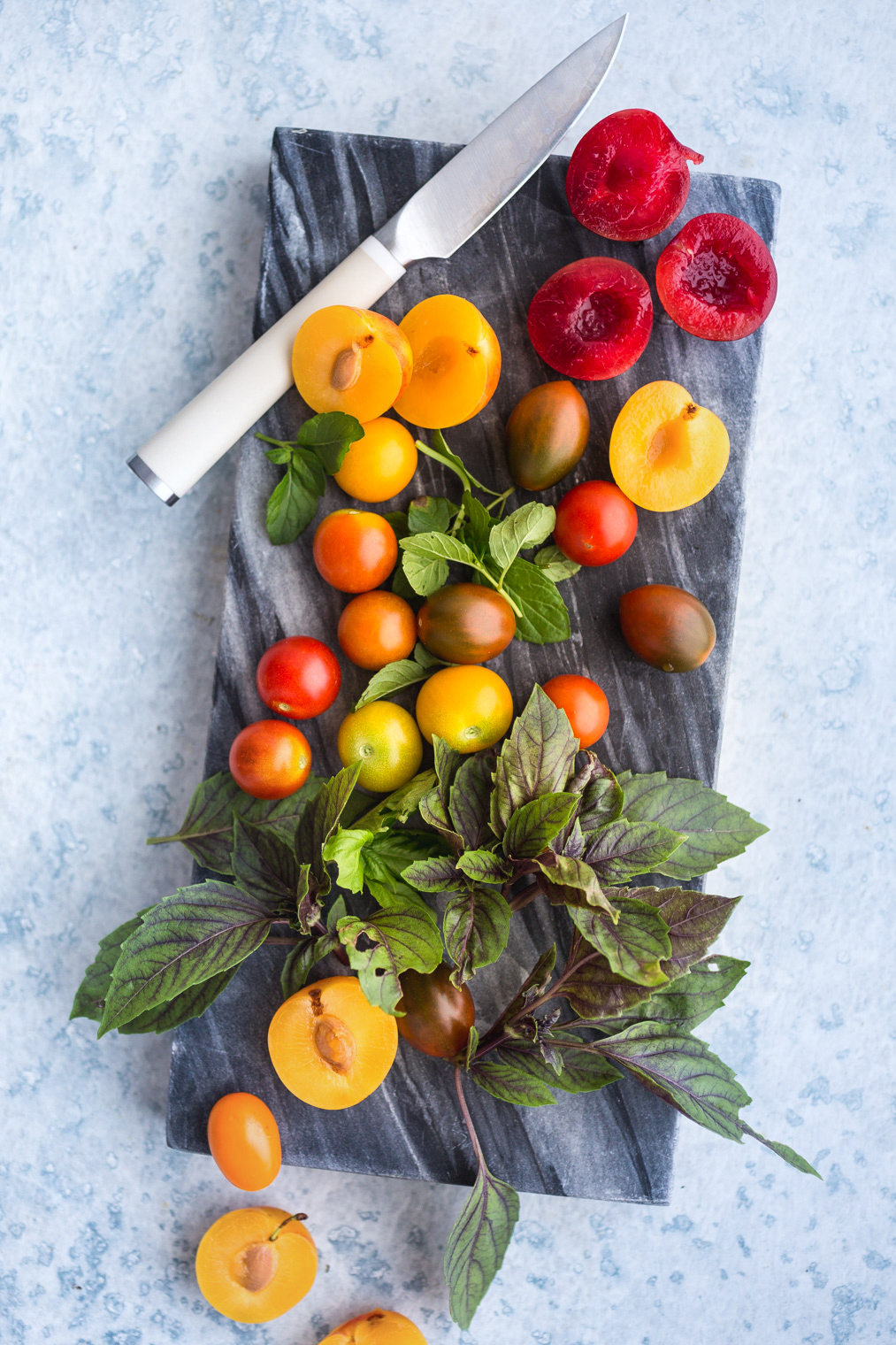 fresh plums, tomatoes, and herbs on gray serving board