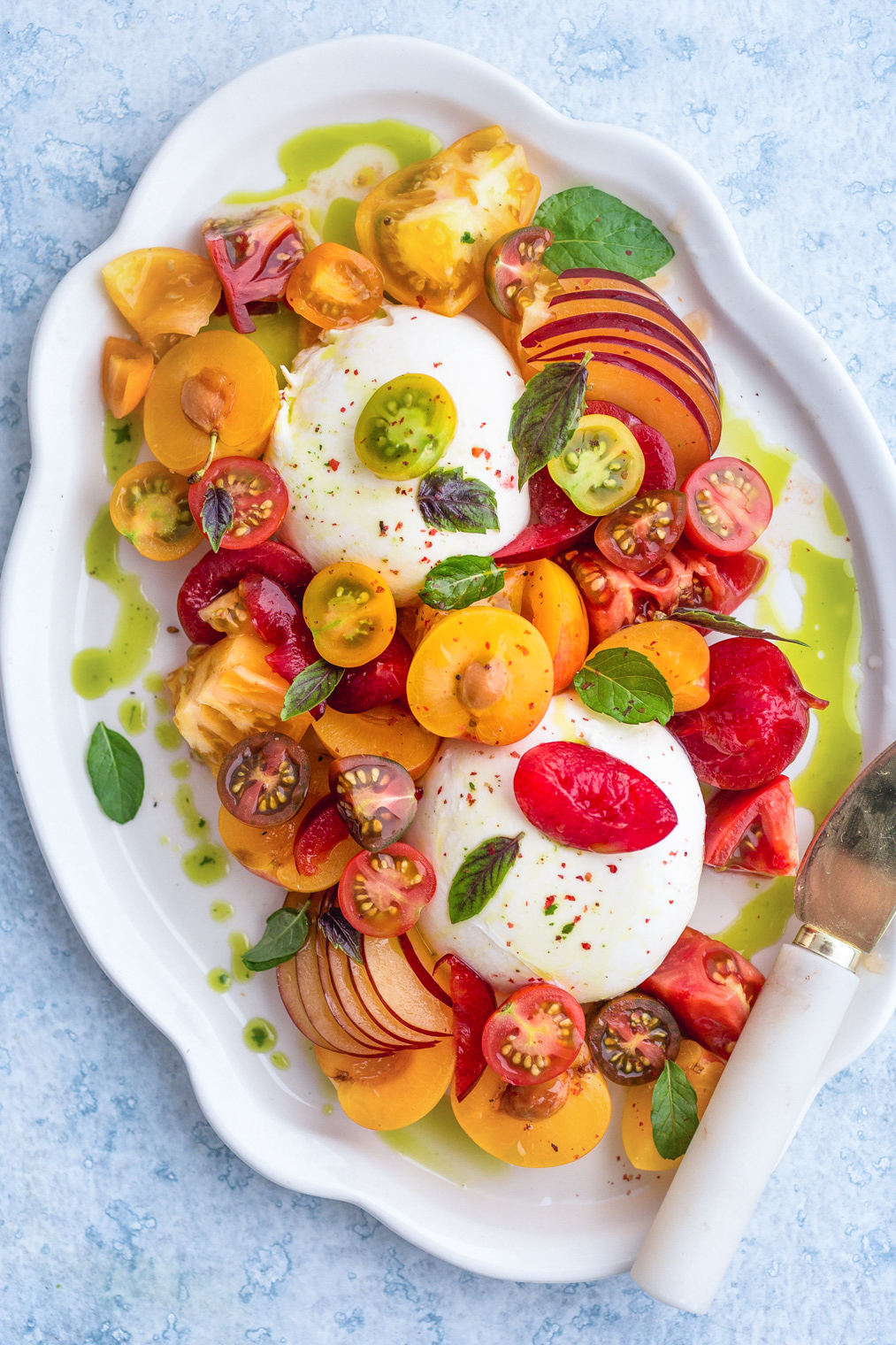 overhead view of Burrata caprese with Plums Tomatoes and Mint-Basil Oil on white serving platter