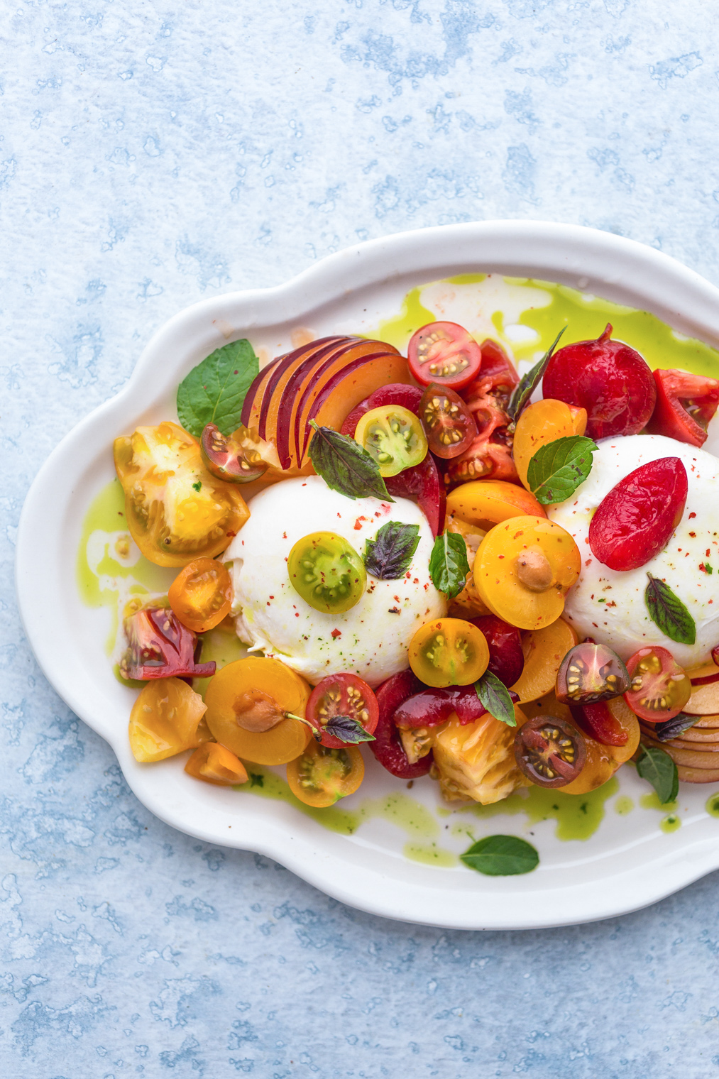 Burrata caprese with Plums Tomatoes and Mint-Basil Oil on white serving platter