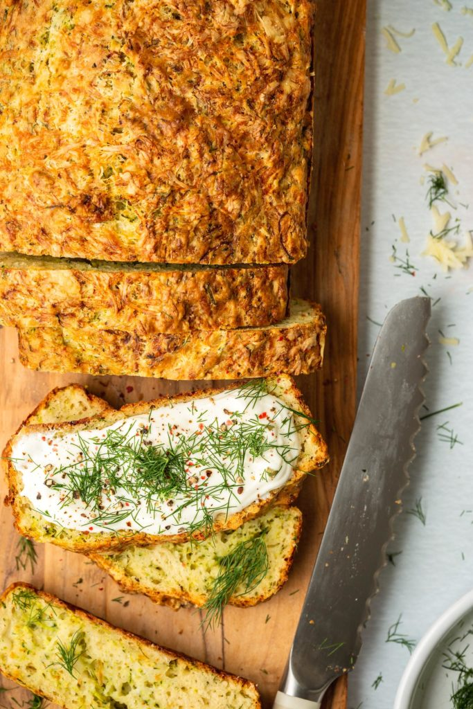 slices of zucchini cheesy bread on wood cutting board topped with whipped goat cheese and dill