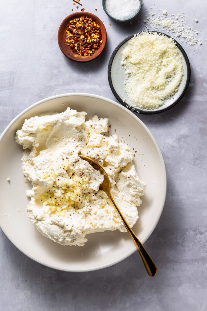 ricotta cheese mixture in white bowl with spoon sticking out