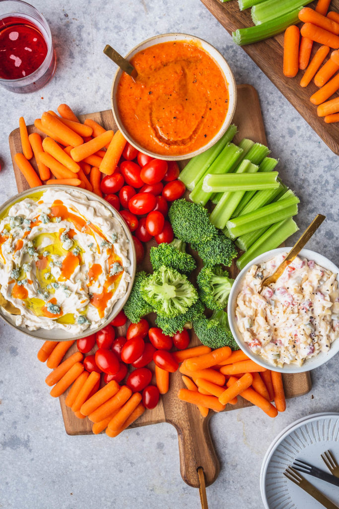3 easy dips in bowls on wood platter with fresh veggies