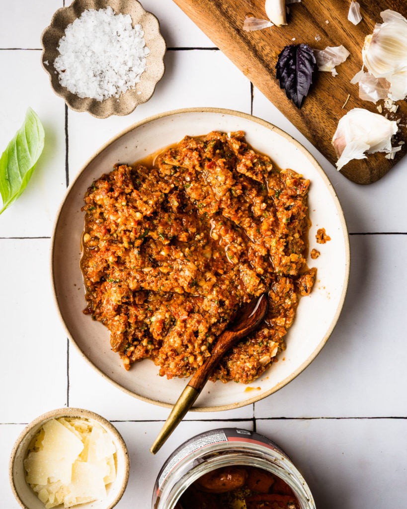 overhead view of Sun Dried Tomato Pesto on white plate with small wood spoon