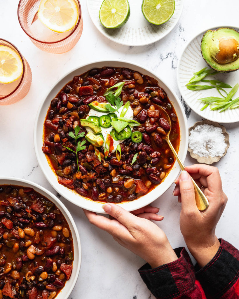 Overhead of the slow cooker vegetable chili with person holding the bowl