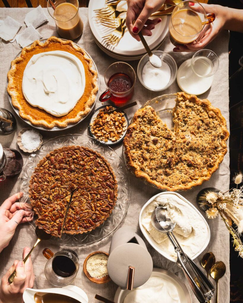 big table spread of thanksgiving pies